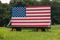 US Stars and Stripes painted on wooden boards in meadow