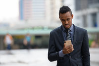 Happy young African businessman using phone in the city