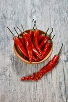 Red chili pepper in a brown clay plate on an old wooden table
