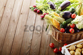 Basket of Organic vegetable food ingredients and crate of potatoes on wood background