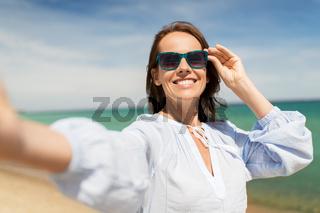 woman in sunglasses taking selfie on summer beach