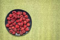 fresh red raspberries on black plate