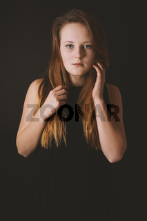 mysterious young lady wearing black dress on black background