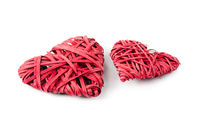 Two red hearts made of straw, isolated on white