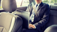 senior businessman with laptop driving in car