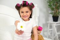Young girl sitting on her bed with flower.