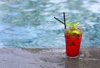 Strawberry Mojito cocktail at the edge of a resort pool. Concept of luxury vacation