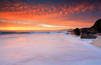 Dramatic red skies and frothy white waves beaches
