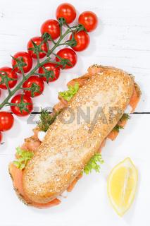 Sandwich Baguette Vollkorn Brötchen belegt mit Lachs Fisch Hochformat von oben auf Holzbrett