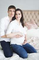 Portrait of the pregnant woman and young man together