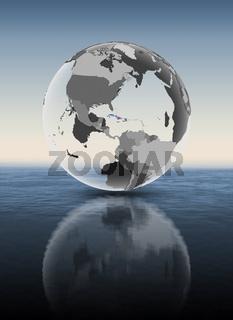 Cuba on translucent globe above water