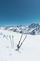 A pair of skis and ski poles stick out in the snow on the mountain slope of the Caucasus against the backdrop of the Caucasian mountain range and the blue sky on a sunny day