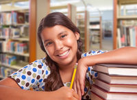 Happy Hispanic Girl Student with Pencil and Books Studying in Library