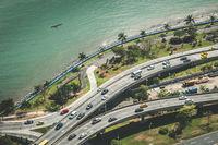 Cars driving on highway near ocean coast - city traffic aerial
