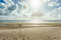 People at the panoramic view of the mud flat sea watching a kitesurfer