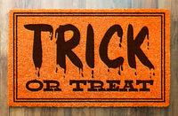 Trick Or Treat Halloween Orange Welcome Mat On Wood Floor Background