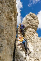 attractive female climbers on a steep Via Ferrata in the Italian Dolomites