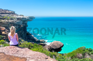 Female sitting on cliffs by the ocean