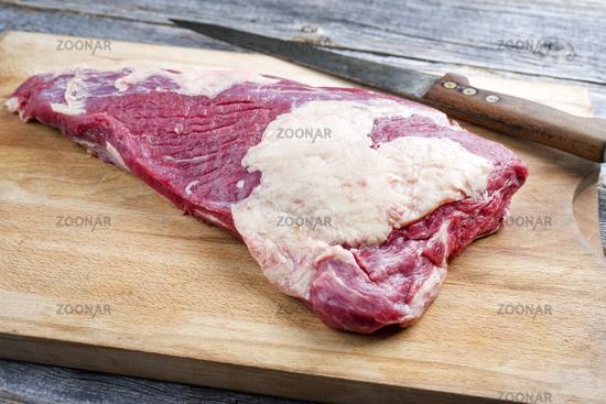 Raw dry aged wagyu tri trip steak as closeup on a wooden board
