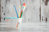 Colorful Plastic Brushes on White Wooden Background