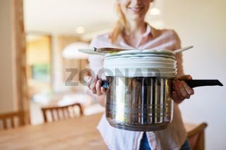 Hausfrau nach dem Abwasch trägt sauberes Geschirr