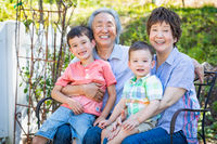 Chinese Grandparents and Mixed Race Children Sit on Bench Outdoors