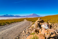 View of Salar de Uyuni with the dormant volcano and a dirty road
