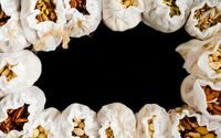 Eco textile bags with various types of nuts on black background, top view, copy space