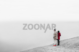 Young lovers in bright clothes standing near the lake and watching calm water. Grey red coloring photo