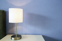 Lamp night light on a night stand with blue wall, space for text