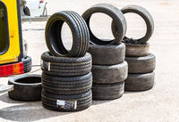 New and used car tires stacked on road
