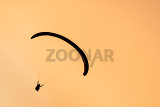 Silhouette of paraglider tandem flying in orange sky