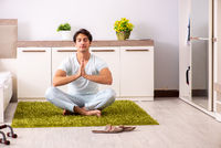 The young man doing yoga in bedroom