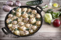 Young potatoes with cottage cheese are baked in the oven.