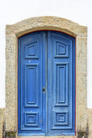 Old wooden blue church door with stone frame