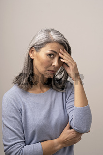 Disappointed Adult Woman of Mongolian Nationality with Gray Hair on a Gray Background.