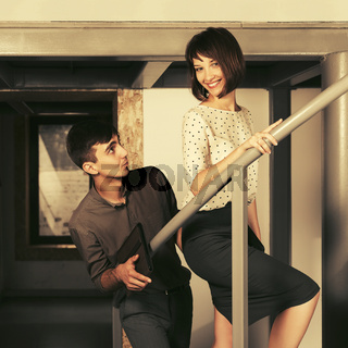 Happy young man and woman flirting in office