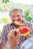 Senior Mann im Sommer beim Melone essen