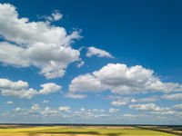 Landscape with beautiful white clouds and fields on a background of blue sky in a sunny day. Aerial view frome drone,