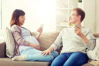husband and pregnant wife with smartphone at home