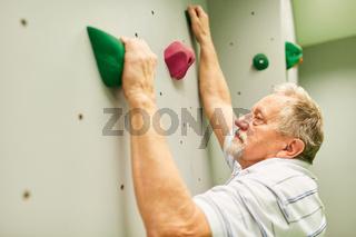 Sportlicher Senior beim Klettern in einer Kletterhalle
