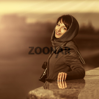 Happy young fashion woman wearing classic coat and headscarf outdoors