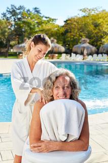 Physiotherapeutin massiert Seniorin den Rücken