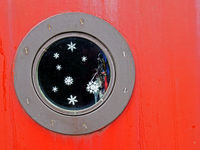 a close up of a round metal porthole on a red boat with snowflakes and glitter on the window and shiny charms hanging inside