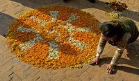 Frau legt ein Mandala aus Blüten,  Boudhanath Stupa, Kathmandu, Nepal