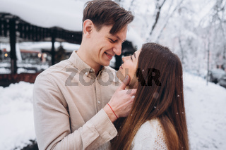 young guy and beautiful girl kiss in a snowy park. Couple in sweaters.