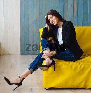 Young woman sitting on yellow sofa