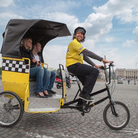 man driving in bicycle taxi