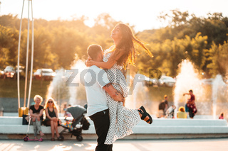 Handsome guy twists a beautiful girl on a background of a fountain