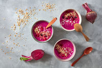 Healthy breakfast bowl with beetroot, oat flakes and berry on stone background, flat lay